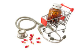 Shopping Cart with capsules and a stethoscope Royalty Free Stock Photography