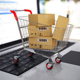 Shopping cart with cardboard boxes on laptop. 3d Royalty Free Stock Image