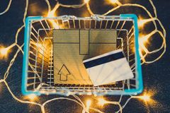 Shopping cart with cardboard parcel and payment card on concrete desk surrounded by fairy lights stock image