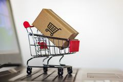 Shopping cart with Carton on computer keyboard. Online shopping, e-commerce and worldwide shipping concept.  royalty free stock photography