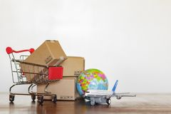 Shopping cart with cartons, airplane and earth globe. Global logistics, shipping and worldwide delivery business concept.  royalty free stock image