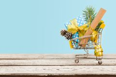 Shopping cart with christmas decoration on wood over blue background.  Royalty Free Stock Image