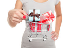 Shopping cart with Christmas gifts for holiday. Miniature shopping cart with Christmas gifts for holiday shopping on boxing day or black friday. Closeup of woman Royalty Free Stock Images