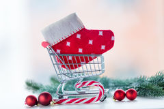 Shopping cart with christmas sock and lolipop. On white background Royalty Free Stock Photos