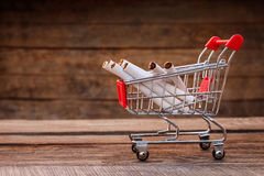 Shopping cart with cigarette. On the old wood background. Toned image Royalty Free Stock Images