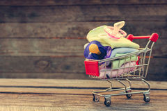 Shopping cart with clothing and baby pacifiers Royalty Free Stock Photo