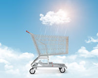 Shopping cart on clouds under rain Royalty Free Stock Image