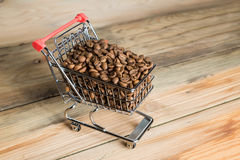 The shopping cart with coffee beans on wooden table Stock Images