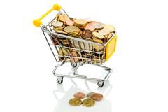 Shopping cart with coins. A shopping cart is well stocked with euro coins, symbolic photo for purchasing power and consumption Royalty Free Stock Photography