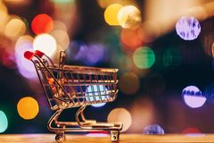Shopping cart with colourful circular bokeh and reflections background. Out of focus Christmas tree Stock Images