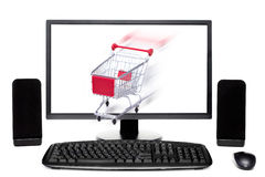 Shopping cart coming out of desktop computer. Shopping cart coming out of desktop computer monitor Stock Photo