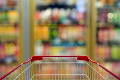 Shopping cart with convenience store refrigerator shelves. Blurred background Stock Images