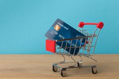 Shopping cart with credit card on blue background. Side view. Advertising of food products and clothing. Finance, well-being, modern payment systems, online Stock Photography