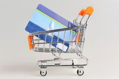 Shopping cart and credit card within on gray Stock Photos