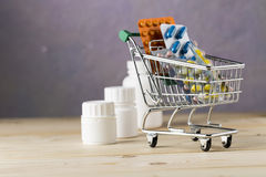 Shopping cart with different tablets and various pill bottle. On wooden table royalty free stock image