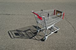 Shopping Cart Empty. A symbol of tough economic times, an empty shopping cart casts a long shadow in a parking lot in Prince Frederick, Maryland USA Royalty Free Stock Photos