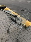 The shopping cart is empty near the parking near the shopping center Royalty Free Stock Photography