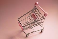 Shopping cart. Empty Supermarket trolley on pink background. Consumerism concept photo. Shopping cart. Empty supermarket trolley on pink background. Consumerism Stock Image
