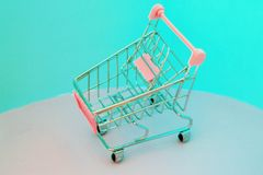 Shopping cart. Empty supermarket trolley on violet background. 90s style glitch effect. Shopping cart. Empty supermarket trolley on violet background Royalty Free Stock Images