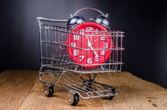 Shopping Cart filled with with alarm clock on wooden board Stock Images