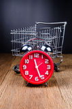 Shopping Cart filled with with alarm clock on wooden board Stock Photography