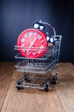 Shopping Cart filled with with alarm clock on wooden board Stock Photo
