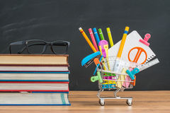 Shopping cart filled with back to school supplies with study gla Royalty Free Stock Photo