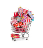 Shopping cart filled with christmas gifts. Stock Photos