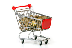 The shopping cart filled in by coins Royalty Free Stock Photo