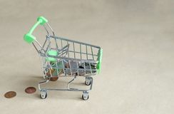 Shopping cart filled with coins, lost money from the basket royalty free stock image
