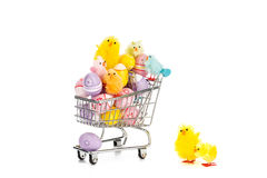 Shopping cart filled with colored easter eggs and happy colored easter chickens. Stock Photos