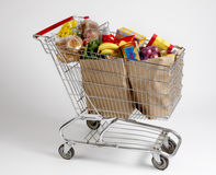 Shopping cart filled with groceries. Shopping cart filled with bagged groceries shot on white with soft shadows Royalty Free Stock Photo
