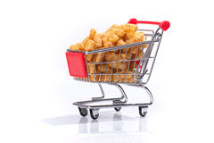 Shopping cart filled with peanut flips. On white background Stock Photos