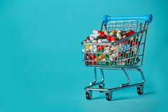 Shopping cart filled with pills. Blue background. royalty free stock photos
