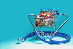 Shopping cart filled with pills with a stethoscope. Blue background. stock image