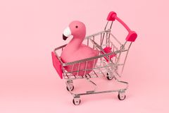 Shopping cart with flamingo. On pink pastel background stock image
