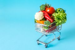 Shopping cart with fresh vegetables close-up. On blue background Stock Photography