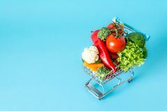 Shopping cart with fresh vegetables close-up. On blue background Royalty Free Stock Photography