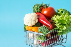 Shopping cart with fresh vegetables close-up. On blue background Stock Photos
