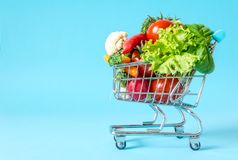 Shopping cart with fresh vegetables close-up. On blue background Stock Photo