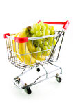 Shopping cart with fruit. Shopping cart with bananas and green grapes isolated on white background Stock Photo