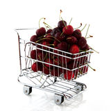 Shopping cart with fruit. Shopping cart with fresh strawberries and cherries Royalty Free Stock Photos