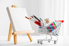 Shopping cart full with artistic goods for drawing and canvas on easel. Mini shopping cart full with artistic goods for drawing and canvas on easel. Art shop Stock Photo