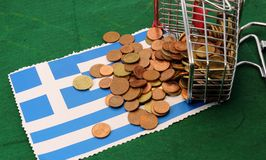 Shopping cart full of coins euro toppled over Flag of Greece Stock Photo
