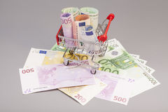 Shopping cart full of euro banknotes isolated Stock Image