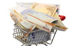 Shopping cart full of euro banknotes on white background Royalty Free Stock Photos