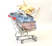 Shopping cart full of euro banknotes on white background Stock Image