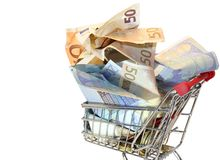 Shopping cart full of euro banknotes on white background Royalty Free Stock Images