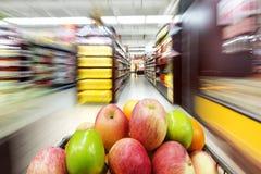 A shopping cart full of fruit on store shelves Stock Photography