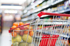 A shopping cart full of fruit on store shelves Royalty Free Stock Photos